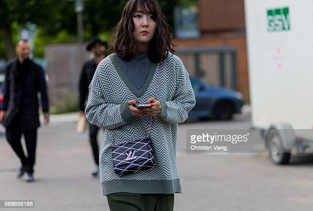 A guest wearing a green vneck sweater and Louis Vuitton bag outside Ganni during the second day of the Copenhagen Fashion Week Spring/Summer 2017 on...