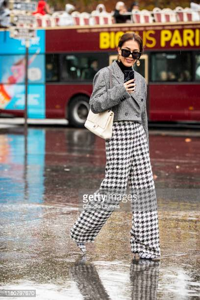 Guest, wearing a grey cropped blazer, black and white pants and cream bag, is seen outside the Chanel show during Paris Fashion Week - Womenswear...