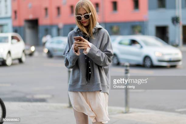 A guest wearing a grey hoody during the MercedesBenz Fashion Week Berlin Spring/Summer 2018 at Kaufhaus Jandorf on July 6 2017 in Berlin Germany