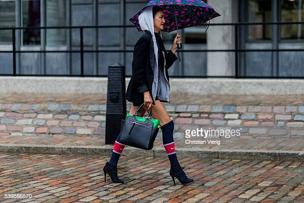A guest wearing a grey hoody umbrella heels and navy Nike socks outside Belstaff during The London Collections Men SS17 on June 12 2016 in London...