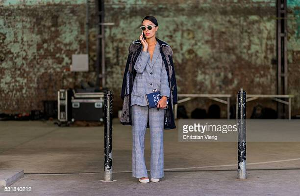 A guest wearing a grey plaid suit and black wool coat with fur outside By Johnny at MercedesBenz Fashion Week Resort 17 Collections at Carriageworks...