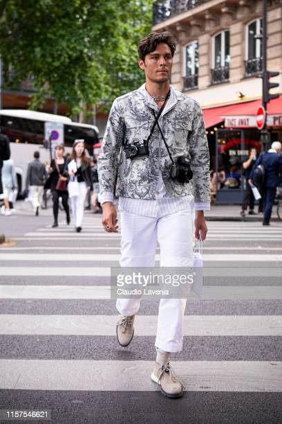 A guest wearing a grey printed jacket white pants and beige shoes is seen outside Dior fashion show on Day 4 during the Paris Fashion Week...