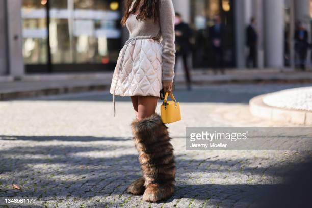 Guest wearing a grey pullover and a rose skirt with brown fur boots outside Miu Miu Show on October 05, 2021 in Paris, France.