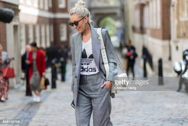 A guest wearing a grey suit outside Simone Rocha during London Fashion Week September 2017 on September 16 2017 in London England