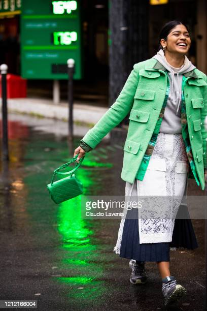 Guest, wearing a grey sweatshirt, blue and white skirt with lace details, green jacket, green Chanel bag and grey sneakers, is seen outside Sacai,...