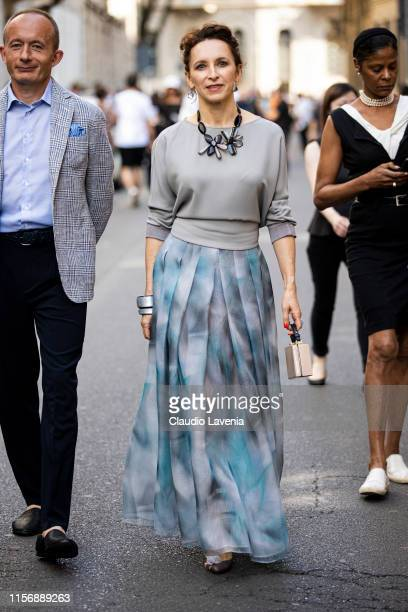 Guest, wearing a grey top, blue and grey printed long skirt, decorated necklace and mini beige purse, is seen outside Giorgio Armani show, during the...