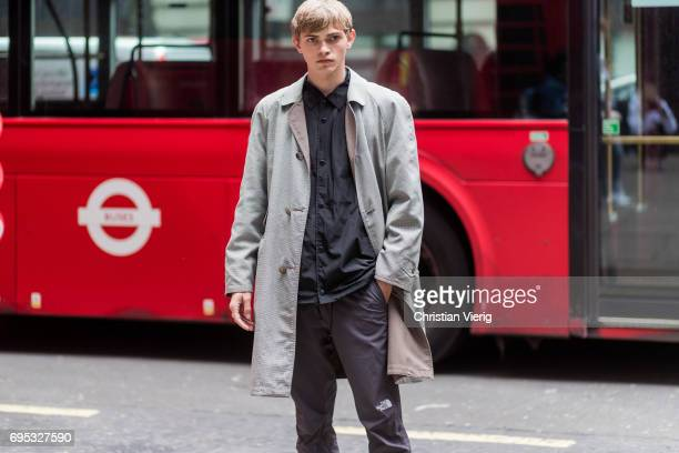 A guest wearing a grey trench coat during the London Fashion Week Men's June 2017 collections on June 12 2017 in London England