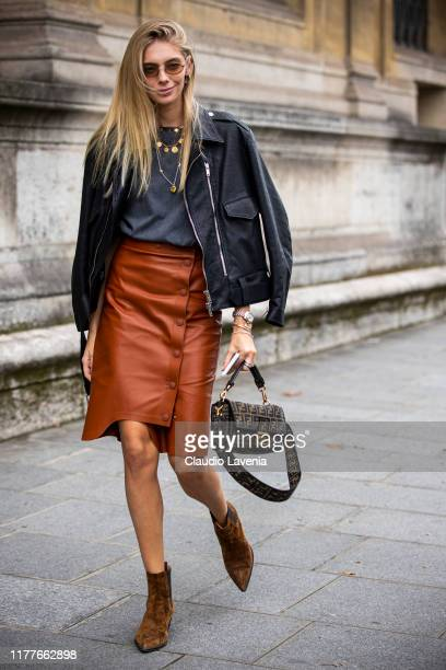 Guest, wearing a grey t-shirt, orange leather skirt, black leather jacket, brown boots and Fendi bag, is seen outside the Unravel show during Paris...