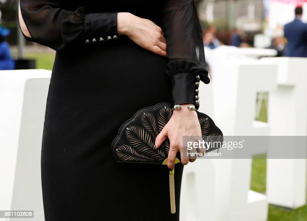 A guest wearing a Kate Spade clutch Alexander McQueen bangle and House of K'dor ring at TAB Everest Day at Royal Randwick Racecourse on October 14...