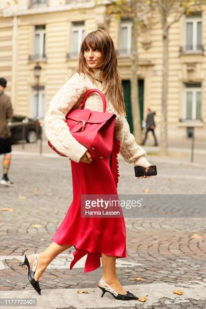 Guest wearing a knit top, pink silky skirt and Dior shoes outside the Altuzarra show during Womenswear Spring/Summer 2020 show Paris Fashion Week on...