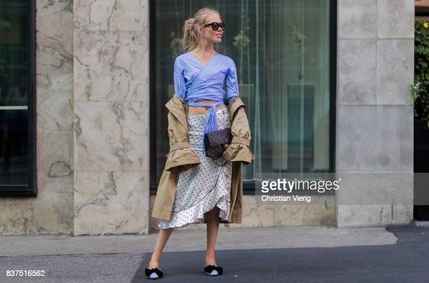 A guest wearing a knotted cropped top trench coat Chanel bag skirt outside Moods of Norway on August 22 2017 in Oslo Norway