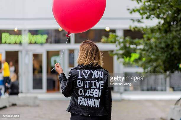 A guest wearing a leather jacket with the saying I Love You But I've Chosen Fashion holding a red balloon outside Revolver Fair during the third day...