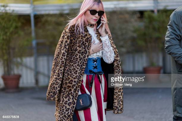 A guest wearing a leopard print coat corset laced top striped pants outside Missoni during Milan Fashion Week Fall/Winter 2017/18 on February 25 2017...