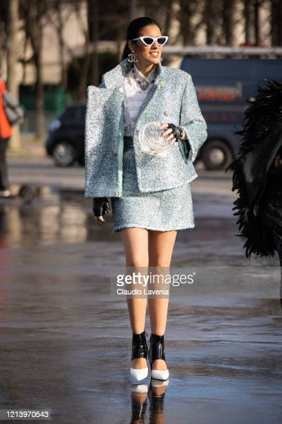 Guest, wearing a light blue decorated jacket with matching mini skirt, white lace shirt, Chanel heels and see-through Chanel bag, is seen outside...