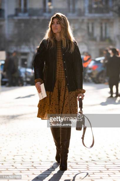 A guest wearing a light brown mini dress black leather jacket black boots and black bag is seen outside Lanvin on Day 3 Paris Fashion Week...