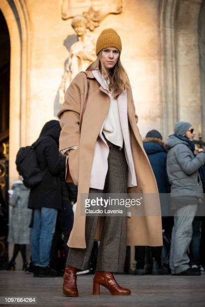 A guest wearing a long beige coat grey check pants brown boots white bag and yellow hat is seen outside Schiaparelli during Paris Fashion Week Haute...