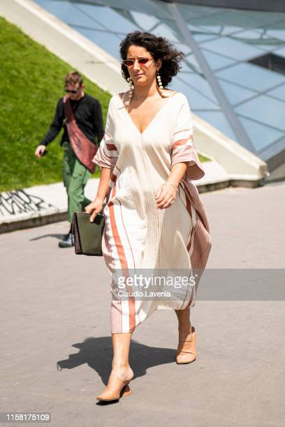 A guest wearing a long beige printed dress green purse and beige heels is seen outside Kenzo fashion show on Day 6 during the Paris Fashion Week...