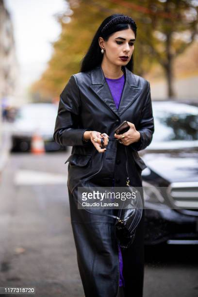 Guest, wearing a long black leather coat, black bag and black headband, is seen outside the Afterhomework show during Paris Fashion Week - Womenswear...