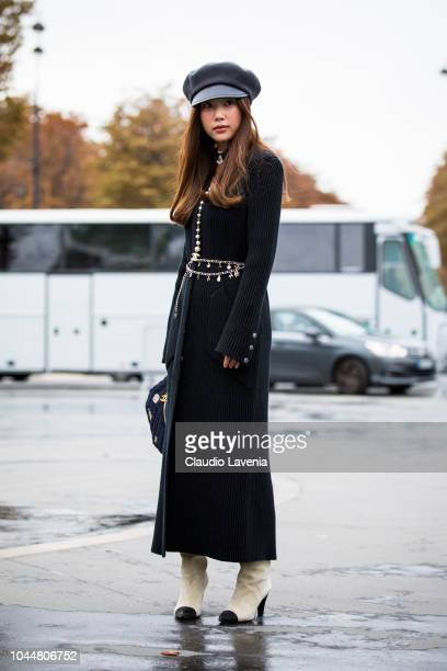 A guest wearing a long knitted dress Chanel belt black baker boy hat white boots and Chanel fanny pack is seen before the Chanel show on October 2...