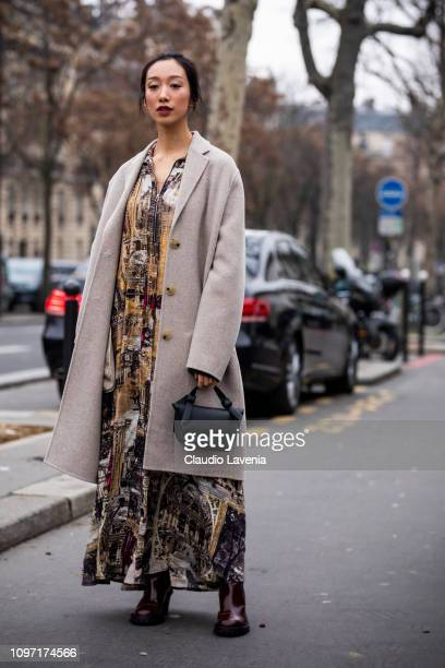 A guest wearing a long printed dress long beige coat brown boots and black Acne bag is seen in the streets of Paris before the Acne Femme show on...