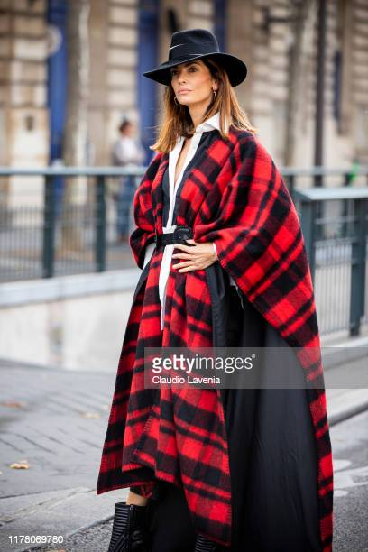 A guest wearing a long red and black checked cape black boots and black hat is seen outside the Redemption show during Paris Fashion Week Womenswear...
