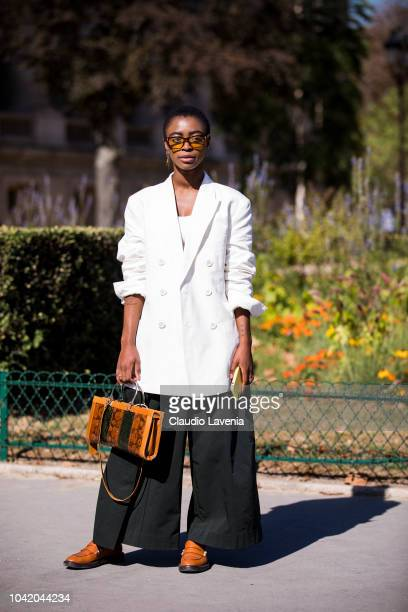 A guest wearing a long white blazer black pants orange loafers and snake print bag is seen before the Paco Rabanne show on September 27 2018 in Paris...
