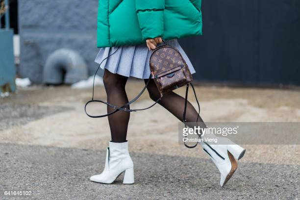 A guest wearing a Louis Vuitton backpack white ankle boots outside Lacoste on February 11 2017 in New York City