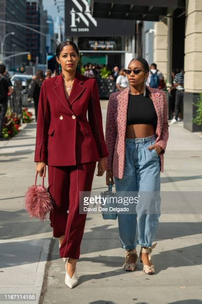 Guest wearing a maroon suit, pink feather purse, with white shoes and a guest wearing a pink jacket, black crop top, and high waist jeans attend New...