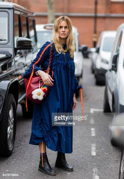 A guest wearing a navy dress red bag black boots outside Anya Hindmarch on day 3 of the London Fashion Week February 2017 collections on February 19...