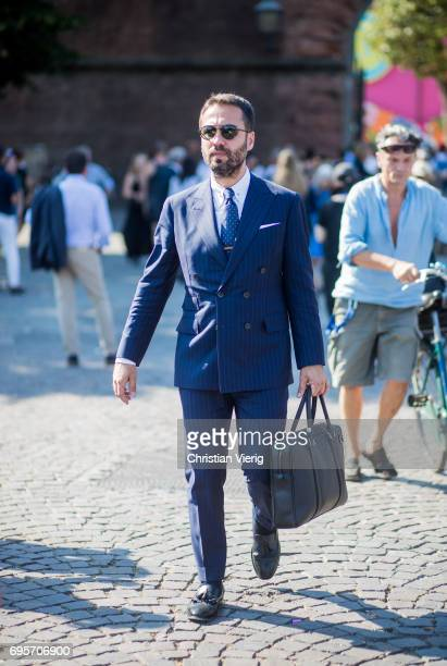 A guest wearing a navy suit an hand bag is seen during Pitti Immagine Uomo 92 at Fortezza Da Basso on June 13 2017 in Florence Italy