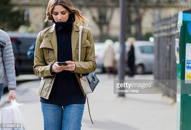 A guest wearing a navy turleneck denim jeans and an olive leather jacket outside Dries van Noten during the Paris Fashion Week Womenswear Fall/Winter...