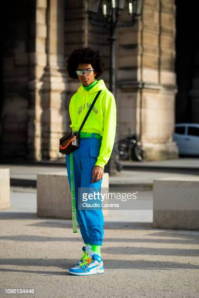A guest wearing a neon green jumper blue cargo pants colorful Nike sneakers and a Louis Vuitton bag is seen in the streets of Paris after the...