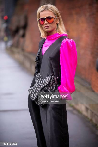 Guest, wearing a neon pink blouse, black jumpsuit, red Carrera sunglasses and Dior bag, is seen outside Balmain on Day 5 Paris Fashion Week...