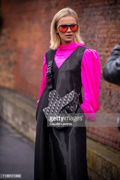 A guest wearing a neon pink blouse black jumpsuit red Carrera sunglasses and Dior bag is seen outside Balmain on Day 5 Paris Fashion Week...