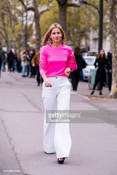 A guest wearing a neon pink sweater white pants and pink bag is seen before the Valentino show on September 30 2018 in Paris France