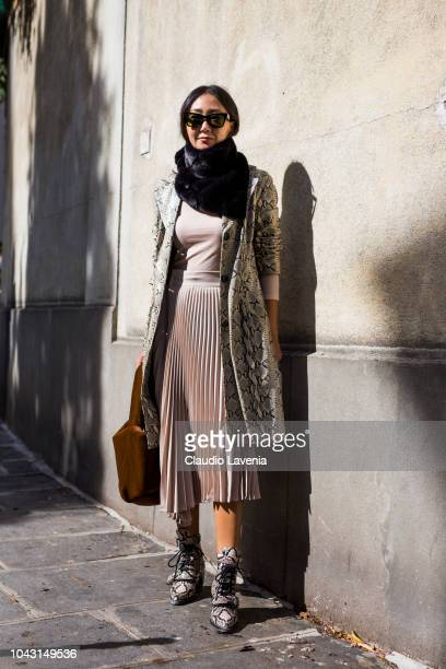 A guest wearing a nude top nude midi skirt snake print boots snake print coat tan bag and black scarf is seen after the Altuzarra show on September...