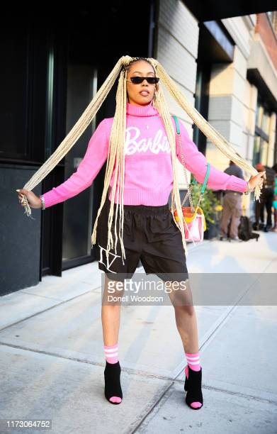 A guest wearing a pink Barbie shirt black shorts black shoes with pink socks and handbag during New York Fashion Week at Spring Studios on September...