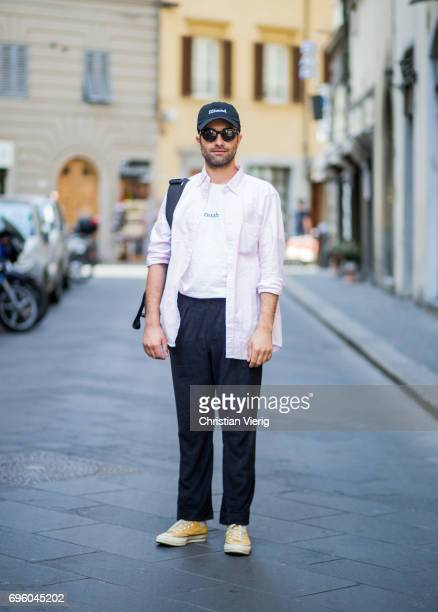 A guest wearing a pink button shirt cap navy pants yellow Converse is seen during Pitti Immagine Uomo 92 at Fortezza Da Basso on June 14 2017 in...
