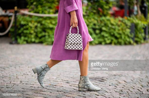 A guest wearing a pink coat ankle boots with snake print during Stockholm Runway SS19 on August 30 2018 in Stockholm Sweden