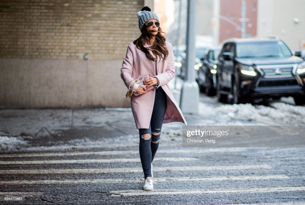 A guest wearing a pink coat, beanie, pink top, denim jeans outside Noon by Noor on February 9, 2017 in New York City.