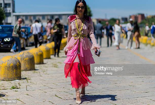 A guest wearing a pink dress outside Gucci during the Milan Men's Fashion Week Spring/Summer 2017 on June 20 2016 in Milan Italy