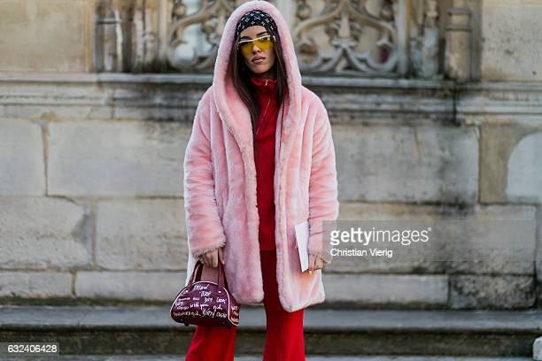 A guest wearing a pink hooded fake fur jacket red suit outside Paul Smith on January 22 2017 in Paris France