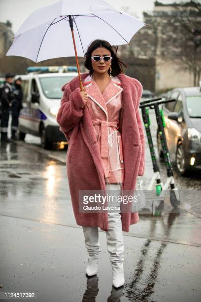 A guest wearing a pink jacket with see through details over the knees white boots white bag and long pink fur coat is seen outside Elie Saab show...
