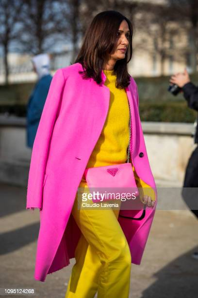Guest wearing a pink neon coat pink neon Prada bag and yellow sweater and pants is seen in the streets of Paris after the OffWhite show on January 16...
