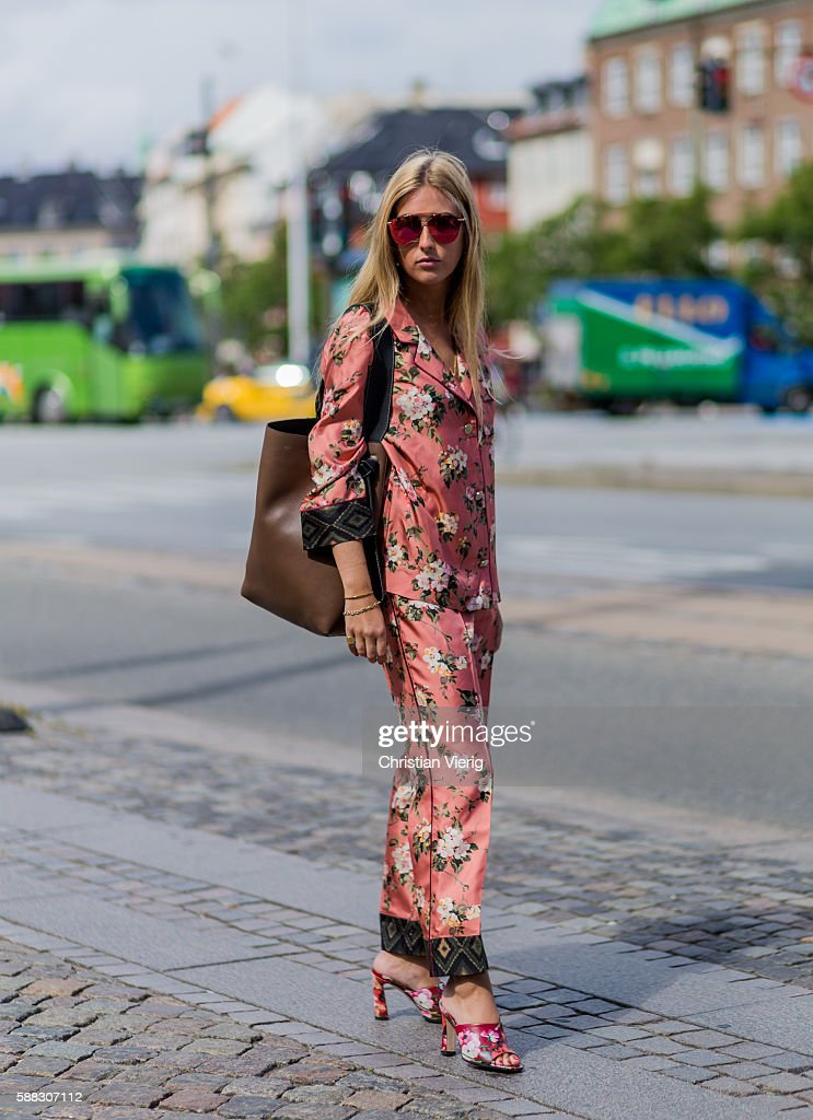 A guest wearing a pink pyjama suit with floral print outside Designers Nest during the first day of the Copenhagen Fashion Week Spring/Summer 2017 on August 10, 2016 in Copenhagen, Denmark.