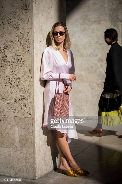 A guest wearing a pink silk midi dress Dior bag and yellow heels is seen before the Dries Van Noten show on September 26 2018 in Paris France