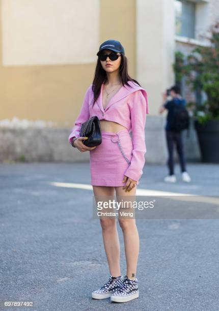 A guest wearing a pink skirt cropped jacket Balenciaga cap Chanel bag is seen outside Malibu 1992 during Milan Men's Fashion Week Spring/Summer 2018...