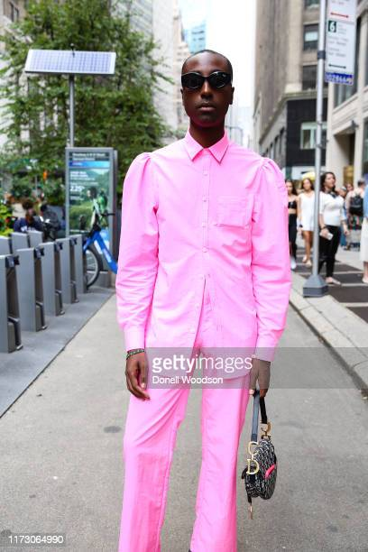 Guest wearing a pink suit and black handbag during New York Fashion Week at Gotham Hall on September 07, 2019 in New York City.