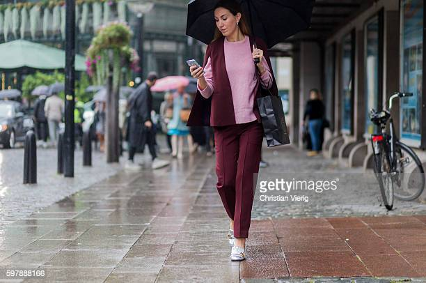 A guest wearing a pink sweater and purple vest and pants and silver Gucci shoes outside The Swedish School of Textiles during the first day of the...