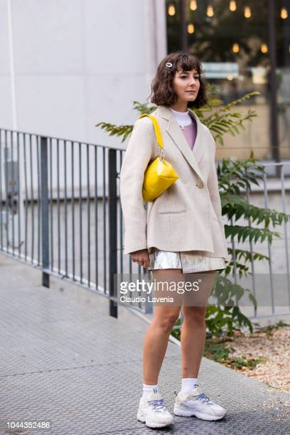 A guest wearing a pink sweater beige blazer gold mini skirt yellow bag and white sneakers is seen before the Sacai show on October 1 2018 in Paris...